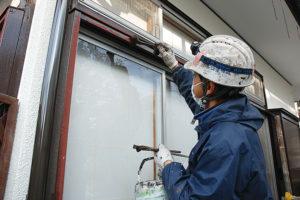 窓の際を塗る職人